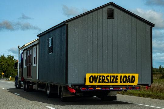 Sheds as oversize load on semi transport truck