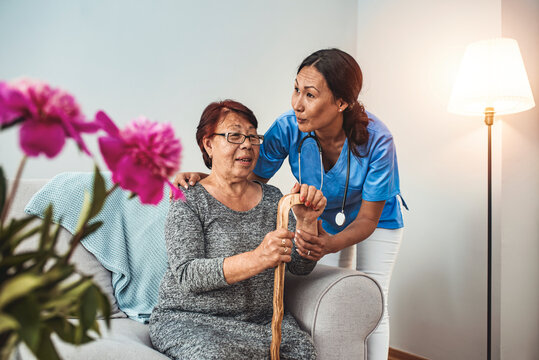 Caregiver, carer hand holding elder hand woman in hospice care. Philanthropy kindness to disabled concept.Public Service Recognition Week. Attentive young doctor talks with female patient