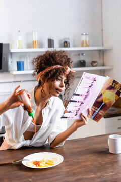 curly woman pouring ketchup on fried eggs and reading magazine