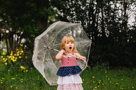 Toddler girl in an American flag dress holding a big, clear umbrella.