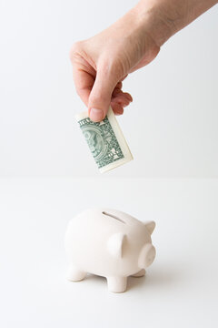 Hand depositing one dollar into ceramic piggy bank