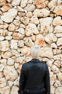 Back view of blonde against stone wall.