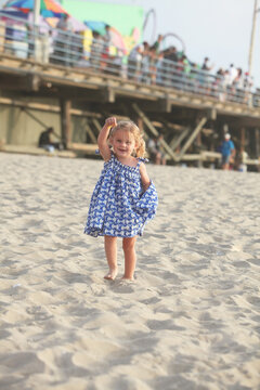 Toddler Wearing Blue and White Checkered Sundress Standing By Pier in Sand