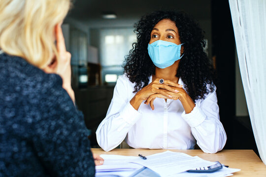 Two people having a business meeting consultation with masks and social distancing due to coronavirus