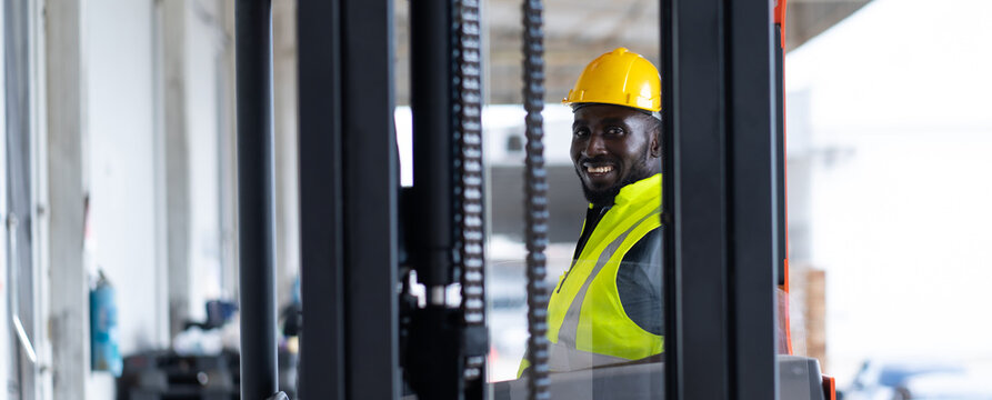 Warehouse man worker driver forklift. warehouse worker driver stacking card boxes by forklift in warehouse store. African American black people.