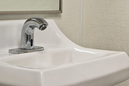 Touchless automated bathroom faucet and sink, angled view showing partial mirror and walls.