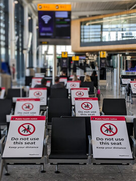 "September 2020, London Heathrow Airport (LHR) - flying during COVID-19 (coronavirus) pandemic, empty terminal, seats closed to maintain social distancing with ""keep the distance"" signs."
