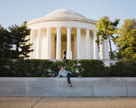 Young boy posing hilariously in front of the Jefferson Memorial