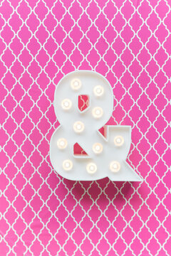 Ampersand marquee light on a pink background
