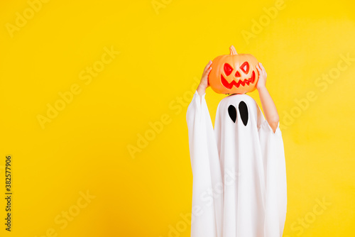 Funny Halloween Kid Concept, little cute child with white dressed costume halloween ghost scary he holding orange pumpkin ghost on hand, studio shot yellow on white background