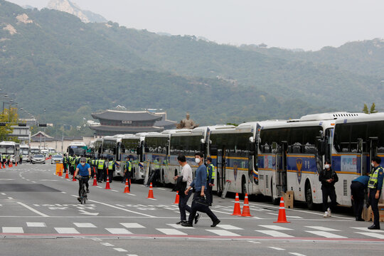 Pedestrians walk past police buses that are parked surrounding the Gwanghwamun square in central Seoul