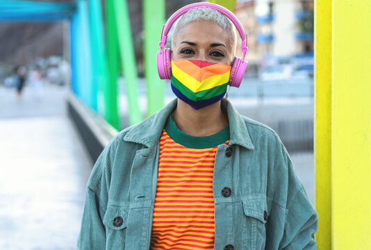 Young woman wearing gay pride mask while listening to music with headphones outdoor - Gender equality and technology concept
