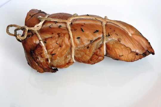 A piece of smoked home made turkey breast trussed with butcher's twine, white background