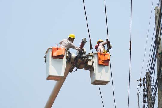 Electricians work together on the electric cable car and electric pole. To maintain the high and low voltage distribution system. They wear a helmet with PPE protection and copy space for your text.