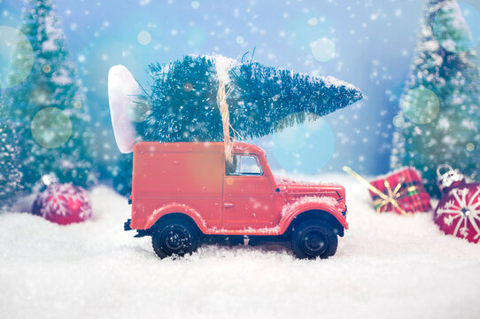 Old miniature truck or oldimer with a christmas tree on the roof driving trough a winterly landscape with some kind of christmas decoration