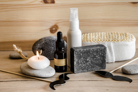 Above view set of various man spa products things. Natural wood disc background with flat sea stones. Gray clay soap bar, beard oil, moisturizing cream, candle burning. Funny mustache shape figurines.