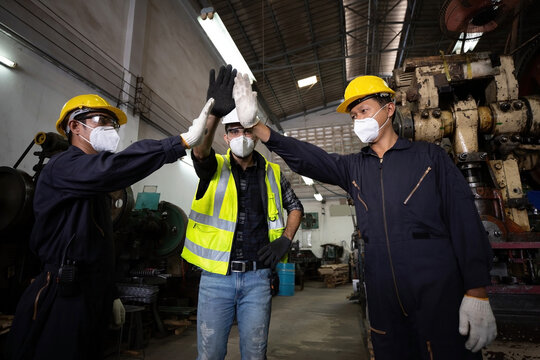 group of industrial technician worker giving high five or raise hands for success the project together in factory, new normal concept
