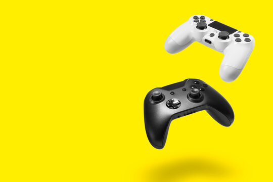 White and black game controllers on yellow background
