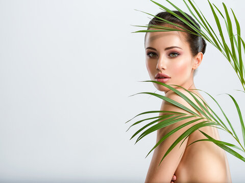 Young beautiful woman with healthy skin of body and palm leaves. Tanned body of an attractive white girl with green plants. Woman hiding her naked body with hands.