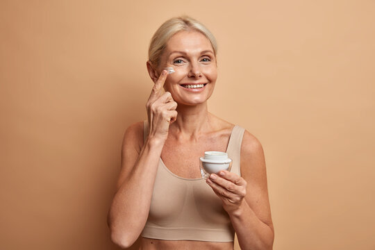 Glad lively European woman of middle age applies anti aging cream on face has natural beauty cares about skin dressed in cropped top holds jar of cosmetic product looks happily at camera poses indoor