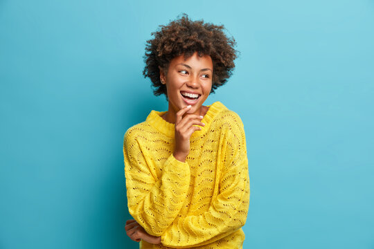 Portrait of nice pleasant looking cheerful woman laughs happily has broad smile and perfect white teeth good mood carefree expression dressed casually poses against blue background. Emotions
