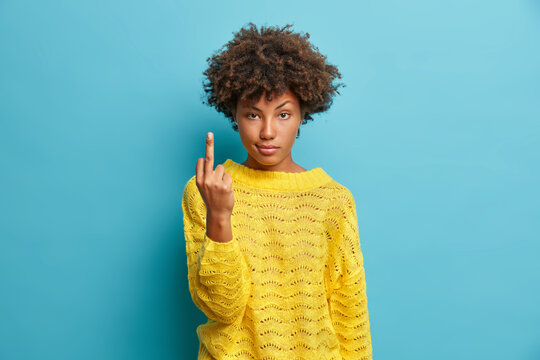 Serious young pretty Afro American woman shows middle finger bad sign asks not to bother her wears yellow sweater isolated on blue background. Body language concept. Provocation and rude attitude