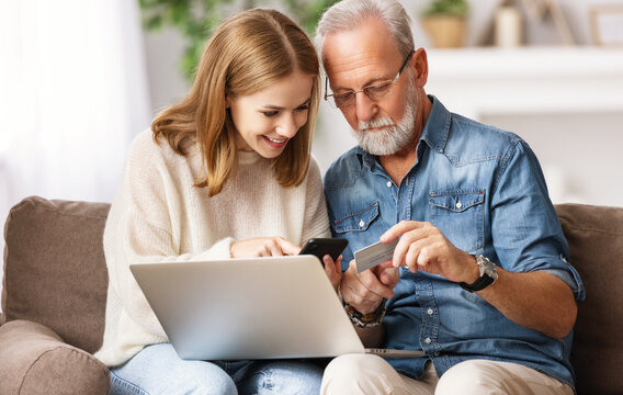 Young woman with father shopping online at home.