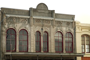 Obraz Second story view of historic stone building on Galveston Island, Texas, with tall, arched windows with red frames, balcony porch and awning, and ceiling fan - fototapety do salonu