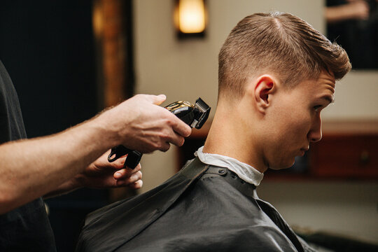 Young man in a barber shop getting his hair clipped