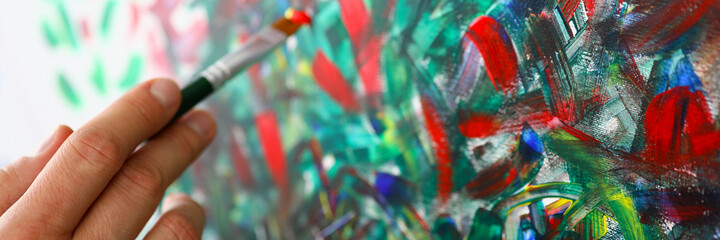 Close-up of persons hand creating abstract painting on canvas holding paintbrush. Picture with...
