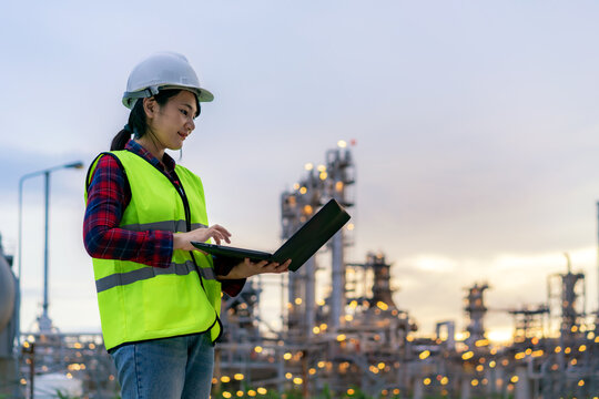 Asian woman petrochemical engineer working at night with notebook Inside oil and gas refinery plant industry factory at night for inspector safety quality control.