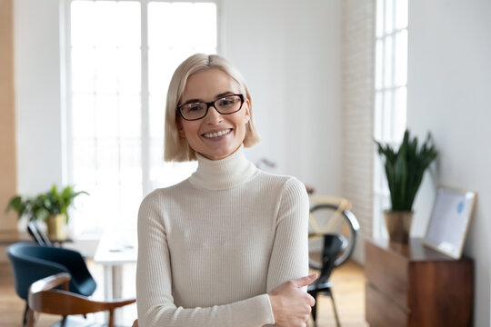 Profile picture of smiling young Caucasian businesswoman in glasses show leadership confidence posing in office. Headshot portrait of happy motivated millennial female employee or worker in eyewear.