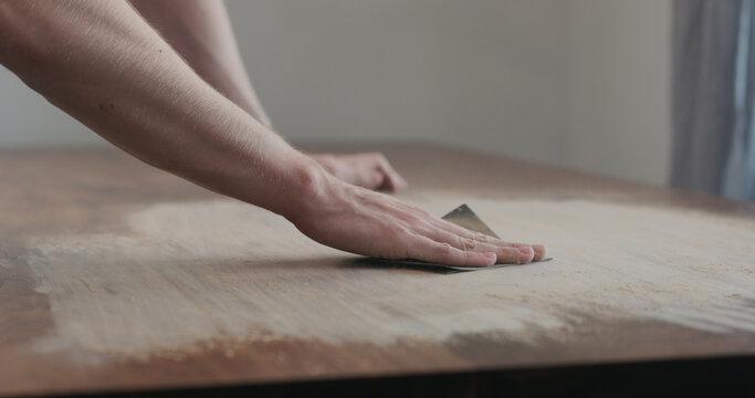 man hand sanding black walnut wood table