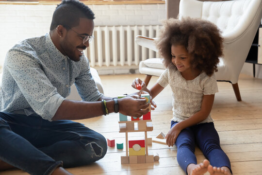 Happy young african ethnicity daddy helping small adorable joyful kid daughter constructing building with wooden blocks, playing on warm floor in living room, enjoying free weekend time at home.