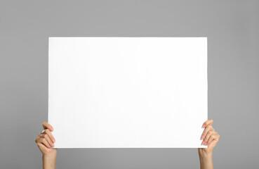 Photo sur Aluminium Fleur Woman holding white blank poster on grey background, closeup. Mockup for design