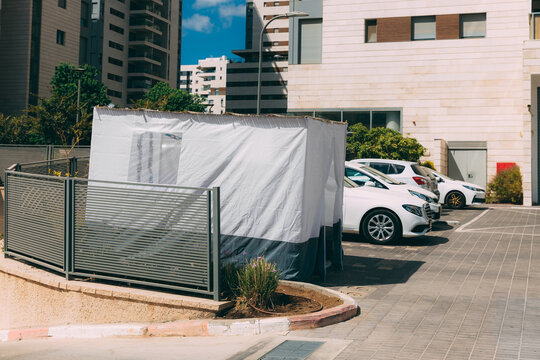 One white blue Sukkah outside on the street with cars near buildings, a traditional building for the Jewish holiday of Sukkot. Jewish tradition. Tragitional Sukkot hut built prior.