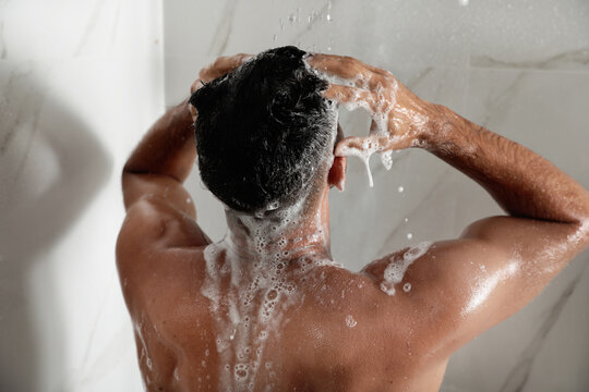 Man washing hair in shower at home, back view