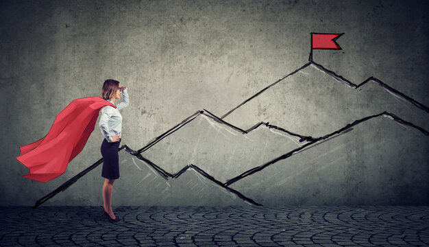Ambitious business woman looking at the top of the mountain with red flag