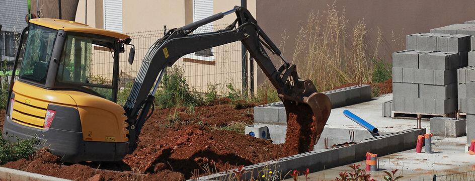 Travaux de terrassement avec une mini pelleteuse sur le chantier de construction d'une maison