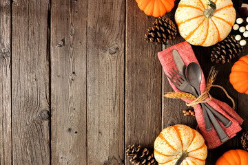 Autumn harvest or thanksgiving table scene with silverware, napkin, pumpkin and decor border against a rustic dark wood background. Copy space.