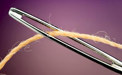 Detalhe macro de linha de costura passando por agulha de costura.