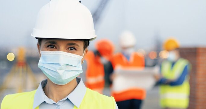 Portrait of female builder or architect wearing protective helmet in construction site. Woman engineer in medical face mask looking at camera.