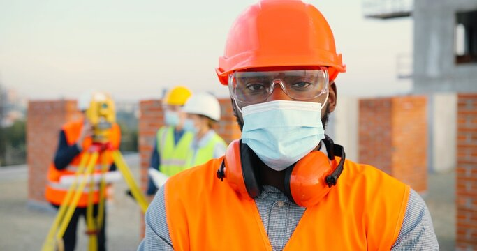 Portrait of African American man builder or construction manager in medical mask and protective helmet with engineer equipment standing on building site.