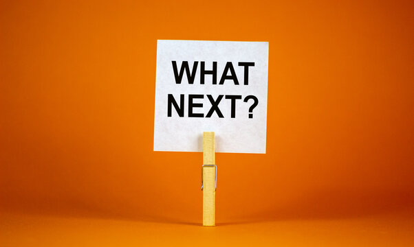 White paper with text 'Whats next', clip on wood clothespin. Beautiful orange background. Business concept. Copy space.