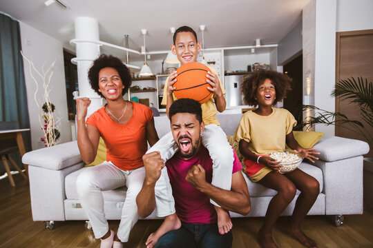 Happy African American family of three watching tv and cheering basketball games on sofa at home.