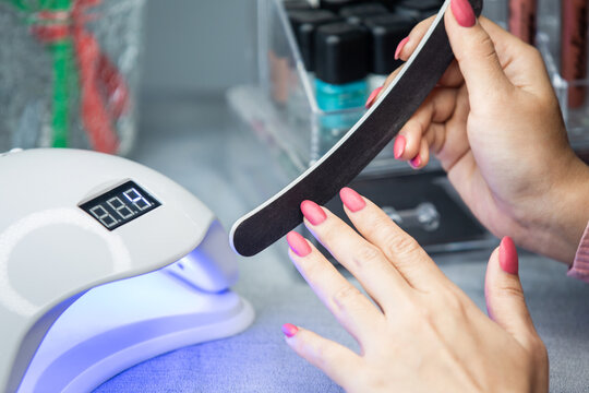 A woman profiling gel manicure with a nail shaper. Self manicure treatment at home. DIY