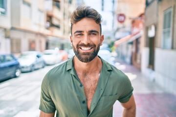 Fototapeta Young hispanic man smiling happy walking at the city