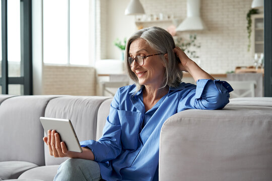 Happy 60s older mature middle aged adult woman holding digital tablet computer conference calling by social distance virtual family online chat meeting or watching video sitting on couch at home.
