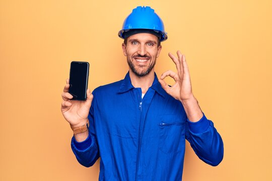 Young handsome worker man wearing uniform and hardhat holding smartphone showing screen doing ok sign with fingers, smiling friendly gesturing excellent symbol