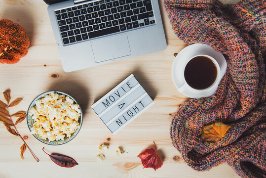 Top view Movie night concept. Flat lay composition with Movie night message on the board, laptop, popcorn bowl, decorative pumpkin, fallen leaves, a cup of tea, and warm plaid on wooden background.